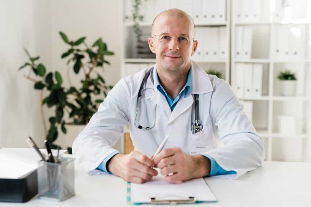Young successful clinician in eyeglasses and whitecoat sitting by desk